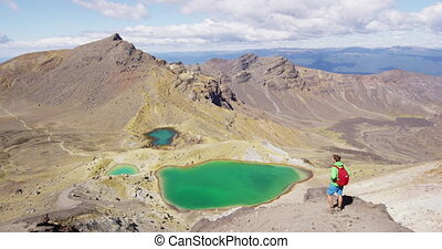 Man Enjoying View From Mountain Nature Landscape Summit Hike overlooking Emerald Lakes. Backpacker hiking on Tongariro Alpine Crossing. Spectacular landscape in Tongariro National Park, New Zealand.