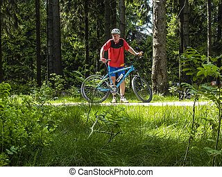 man enjoys riding mountain bike in the forest