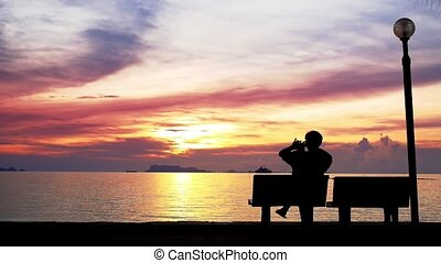 Man Enjoys the Sunset and Takes a Photo.