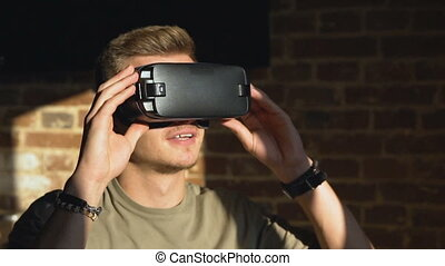 Handsome caucasian man enjoying a virtual reality helm, in front of the brick wall, slow motion