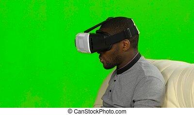 Man enjoys watching videos in VR mask. Green screen