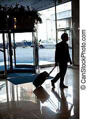 Man entering hotel lobby with his luggage. Car parked in the...