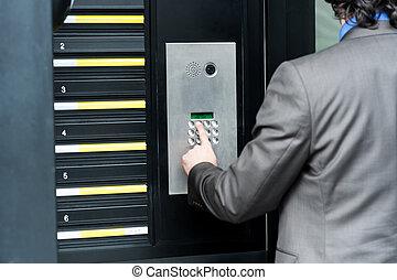 Man entering security code to unlock the door - Businessman...