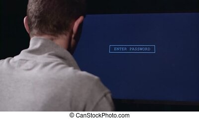 Man enters a password to log in. Back view - Man in a dark,...
