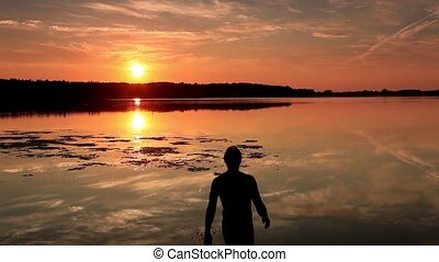 Man enters the lake at sunset