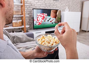 man, eten, popcorn, terwijl, kijkende televisie
