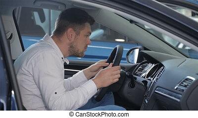 Man examines car interior at the dealership - Young man...
