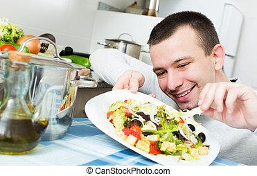 Happy young handsome man examines vegies in home interior