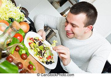Happy young man examines vegies in home interior
