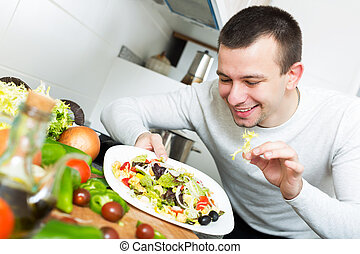 Smiling handsome man examines vegies in home interior