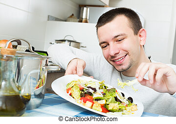 Young handsome man examines vegies in home interior