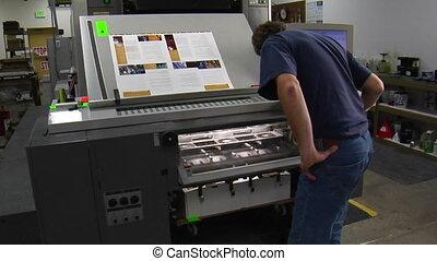 man examines work from printing press