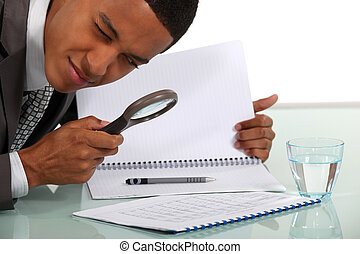 Man examining a document with a magnifying glass