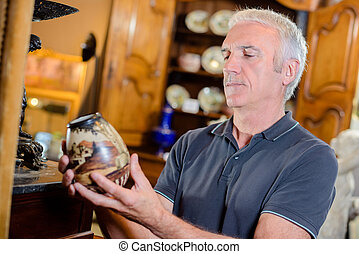 Man examining an antique pot