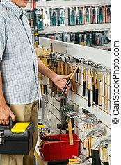 Man Examining Hammer In Hardware Store