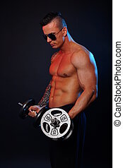 Man exercises with dumbbells