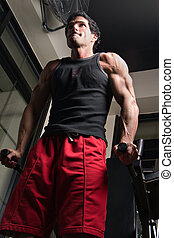 Man Exercising Arm Muscles 5 - Man, with a determined...