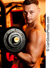 Man exercising his arm muscles by lifting two dumbell free...