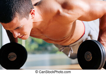 Strong, handsome man doing push-ups in a gym as bodybuilding exercise, training his muscles