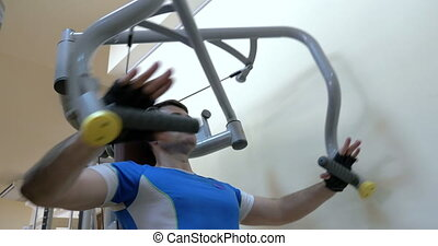 Man exercising on chest press machine - Young man exercising...