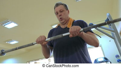 Man exercising with crossbar in the gym - Mature man doing...