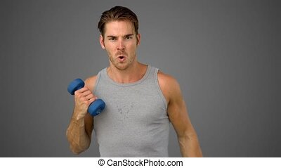 Man exercising with dumbbell on gre