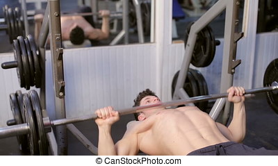 Man exercising With Heavy Weights In The Gym