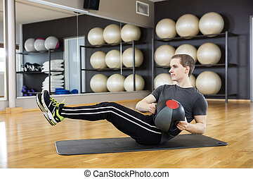 Man Exercising With Medicine Ball In Gym