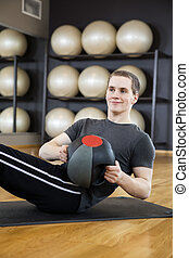 Man Exercising With Medicine Ball On Mat