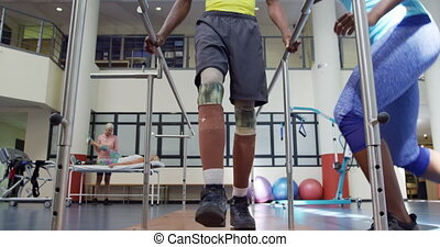 Man exercising with prosthetic legs - Low section front view...