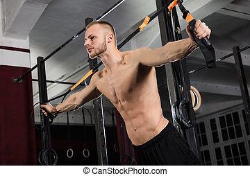 Man Exercising With Suspension Trainer