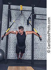 man exercising with trx gym equipment