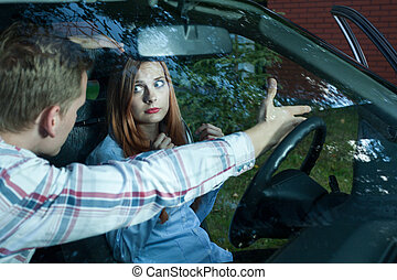 Man expelling woman from a car