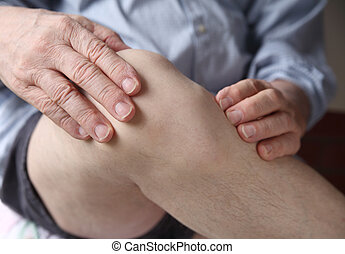 man experiencing sore knee - a man with his hands on a...