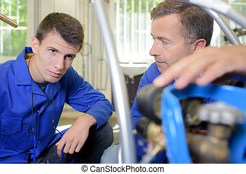 Man explaining controls of gas bottle to apprentice