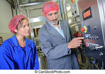 Man explaining controls of machine to woman