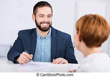 Young businessman explaining documents to female co worker at office desk
