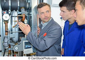 Man explaining machinery to trainees