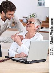 man explaining to senior woman how to use computer