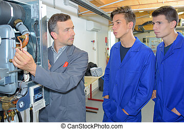 Man explaining workings of boiler to two trainees