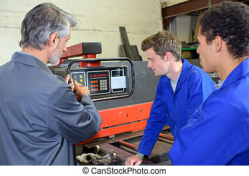 Man explaining workings of machine to two students