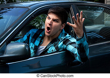 Man Expressing Road Rage - An irritated young man driving a...