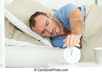 man extend hand reaching to turn off alarm clock switch