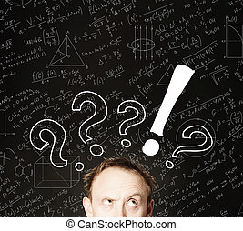 Man face with question mark on blackboard science background. Education, student exam and brainstorm concept