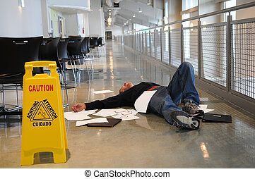Man lies on the wet floor on which he slipped in spite of caution sign, selective focus on man's chin