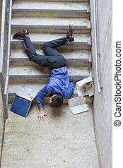 Business man falling down set of stairs.