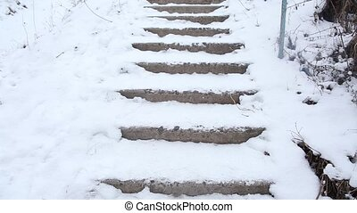 Man falling down the broken stairs. Man is walking up the broken stairs covered with snow. He slips and falls down