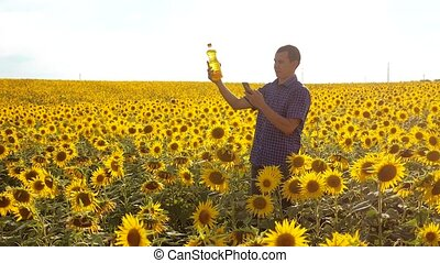 man farmer exploring the field with sunflowers. slow...