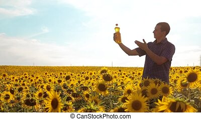 man farmer exploring the field with sunflowers. slow motion...