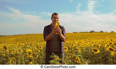 Man farmer hand hold bottle of sunflower oil lifestyle the...